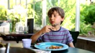 Child eating lunch. Kid eating supper in indoor balcony at home video
