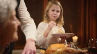 Child enjoying her Thanksgiving turkey slice her granddad served her video