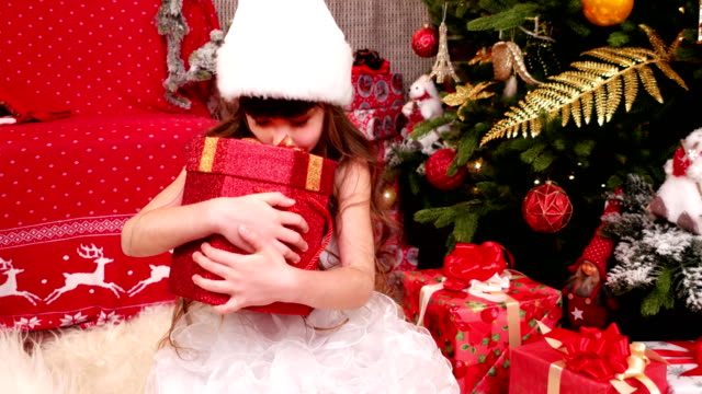 child enjoys the gifts for Christmas, Little girl plays with gifts in the house on Christmas Eve, child carnival costume near the Christmas tree, winter holiday of New Year video