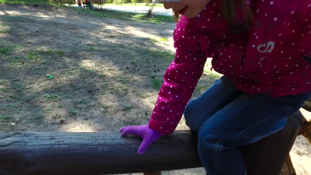 A child girl goes on a wooden log. Girl child running around on the playground in the park. video