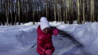 Child girl is dancing on an icy track in the park. The girl is glad that soon become warm. Spring sunny morning. video