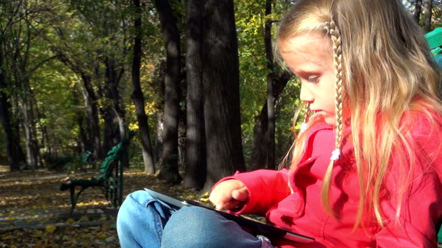 Child, Girl Playing with Tablet, Ipad on Bench in Park video