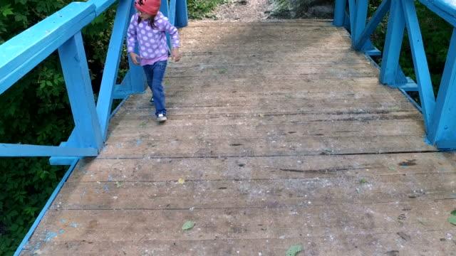 Child girl runs on a wooden bridge. video