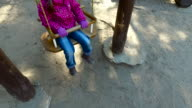 Child girl swinging on a swing in the park. Good spring weather. Sunny day. video