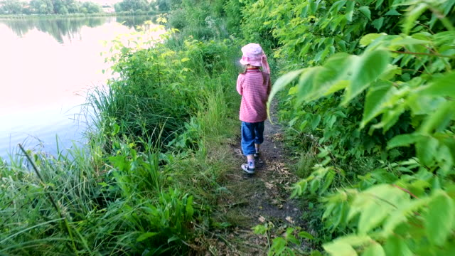 Child girl walking on a narrow path on the bank of the pond. video