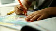Child hands paints a orange pencils on a paper video