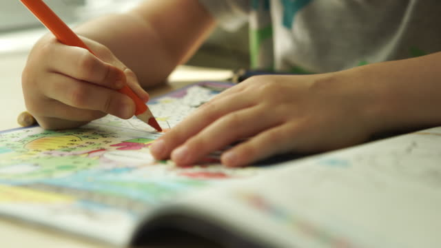 TRACKING: Child hands paints a orange pencils on a paper video
