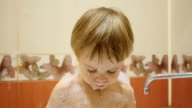 child having fun playing with foam and soap bubbles in the bath video