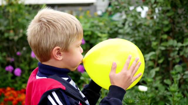 child in the garden inflate a yellow balloon video