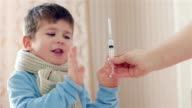 child is afraid of the injection, small boy is sick, medicine syringe in hand, protest against care, medical instruments for injections, kid is afraid and crying video