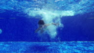 Child jumping into the pool and swims under water video