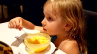 Child little girl eating dessert by spoon. video