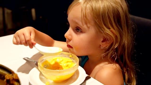 Child little girl eating dessert by spoon. video