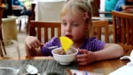 Child little girl eating ice-cream by spoon. video