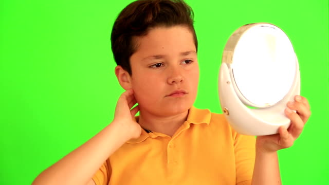 Child lookin at the mirror and brushing his hair video