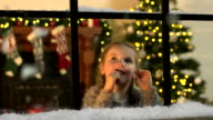 Child looking at Snow falling through window at Christmas video