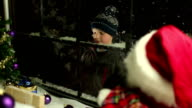 Child looking through shop window at Christmas video