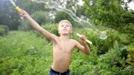 child making big soap bubbles outdoors video