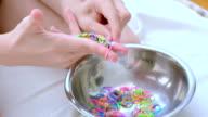 child making multicolored bracelets video