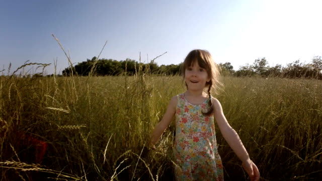 A Child of Tree Playing in the Field of Barley. Lens Flair, Dreamy Look, Slow Motion. video