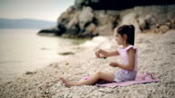 Child on beach throwing stones into water. video