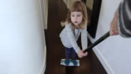 child on mop sliding by mother video