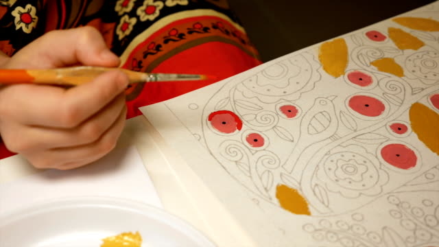Child paints watercolor picture with paint brush video