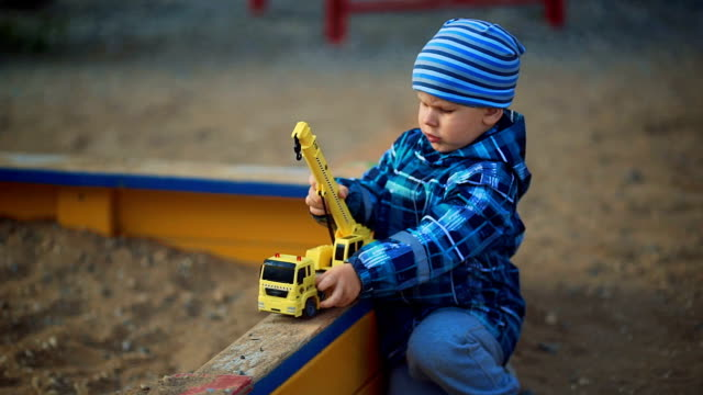 child playing in the sandbox with toy video