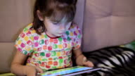 Child playing on ipad tablet pc at home video