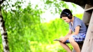 Child playing on the computer with headphones outdoor video