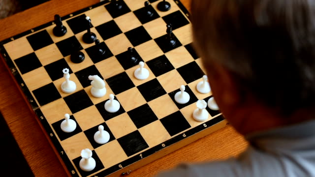 Child playing with grandparents in the chess house video