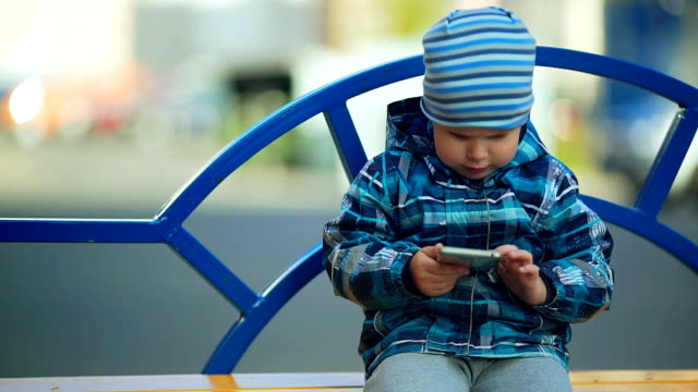 Child playing with smart phone in the park video