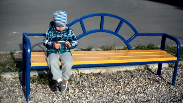 Child playing with smart phone outdoor video