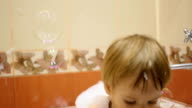 child playing with soap bubbles in the bathroom video