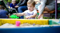 Child playing with toys in sand-pit video