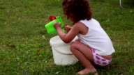 Child playing with water in the bucket video