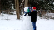 Child Putting a Hat on a Snowman video
