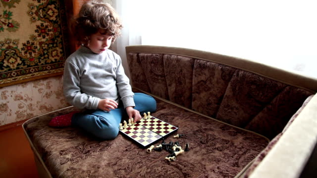 Child putting chess pieces on the chessboard video
