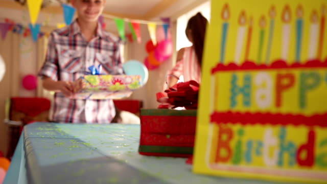 Child Putting Present On Table During Birthday Party At Home video