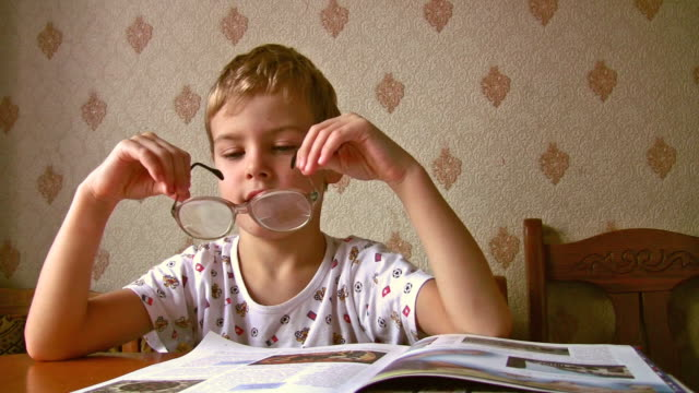Child read book with old glasses video