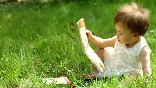Child reading a book on nature, slow motion video