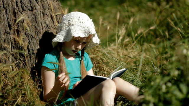 Child reading against a tree video
