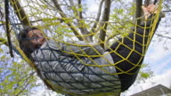 Child Relaxing In Garden Hammock - Stock Video video