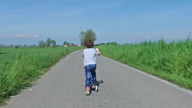 Child riding scooter on country road video