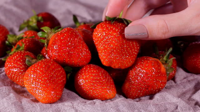 Child rubs his hands. Girl with a large plate of strawberries and looking at camera and child takes berry in hands. HD video
