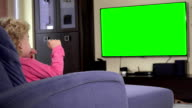 child sit in front of a tv and watch a children show on. Green chroma key screen video