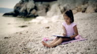Child sits near sea and draws a picture video
