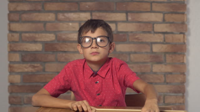 child sitting at the desk holding flipchart with lettering code on the background red brick wall video