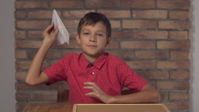 child sitting at the desk holding flipchart with lettering fly on the background red brick wall video