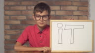 child sitting at the desk holding flipchart with lettering it on the background red brick wall video